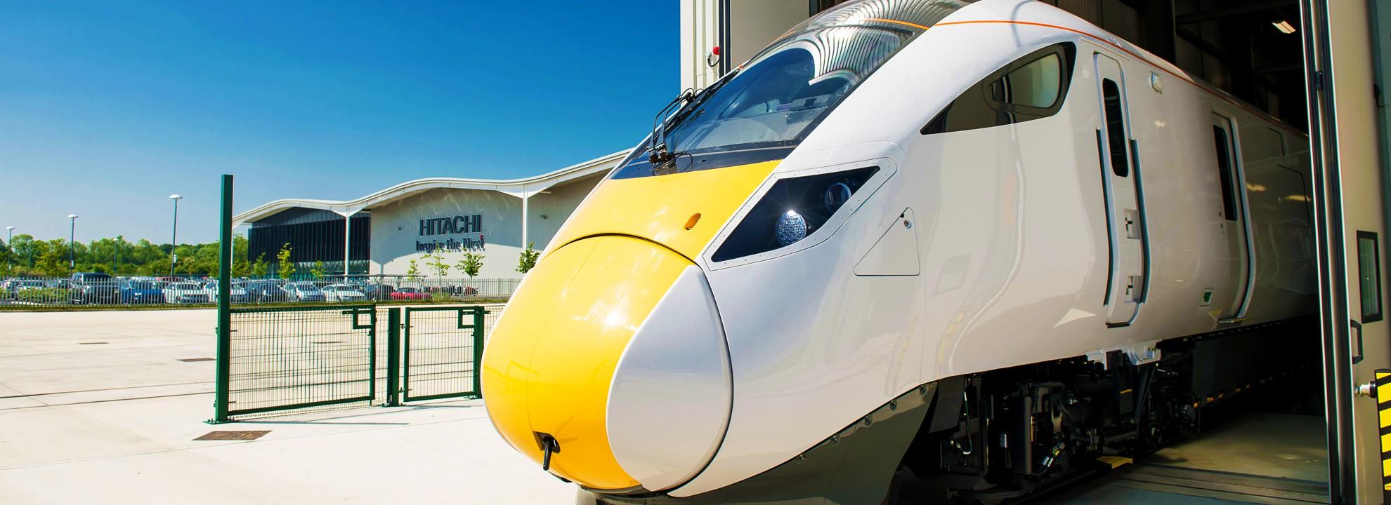 Hitachi train leaving factory building UK
